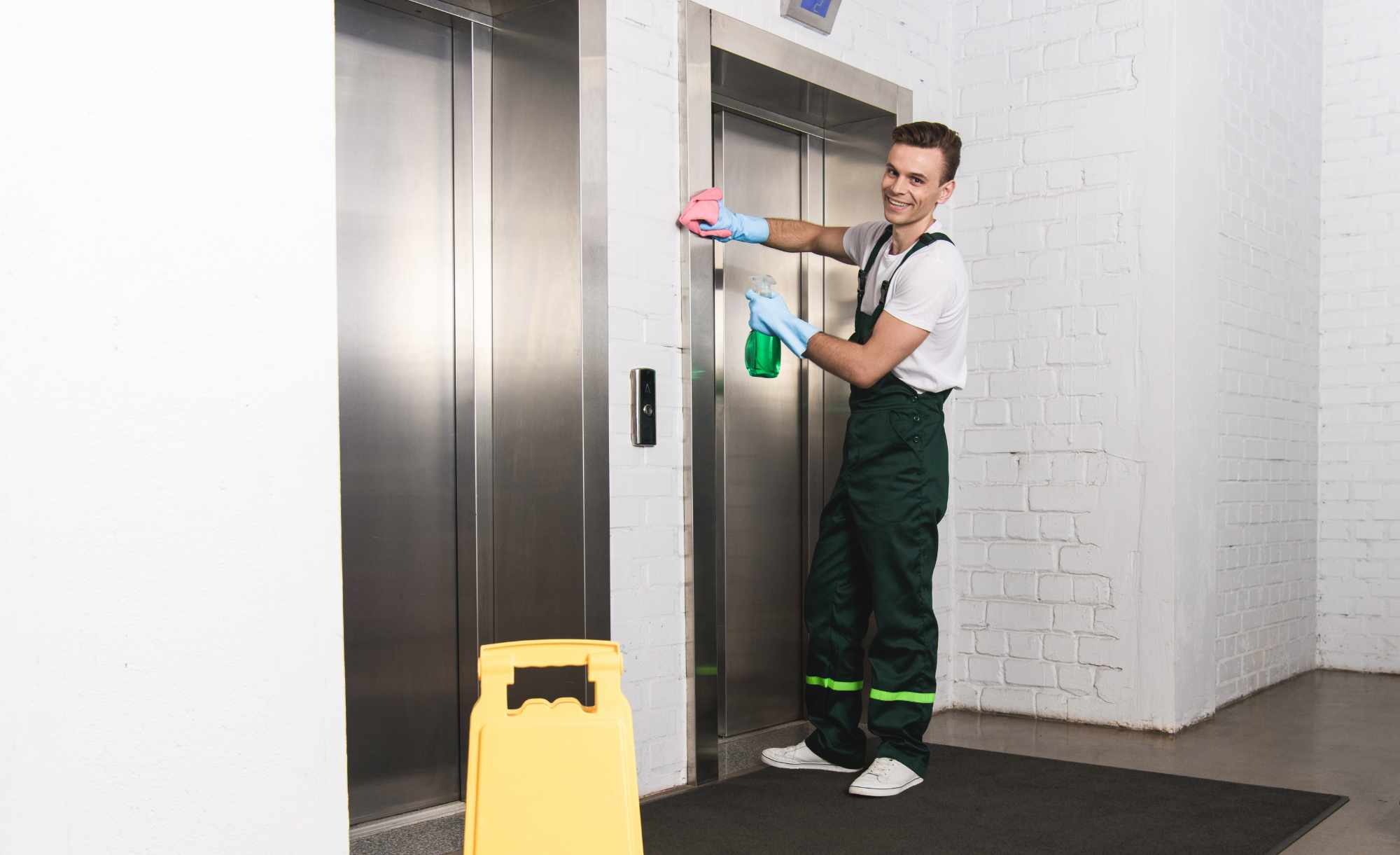 handsome young janitor cleaning elevator and smili WREXFTA 1